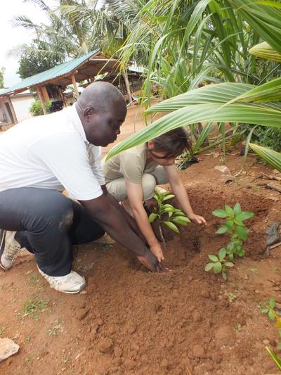 Voluntaria y local trabajando en granja en Togo