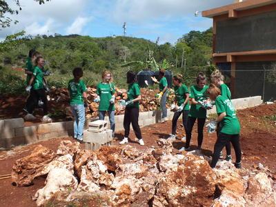 Voluntarios removiendo piedras para construir un patio de juegos en Jamaica