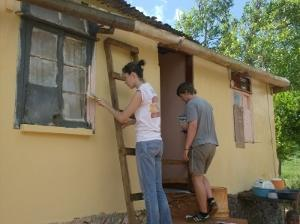 Volunteers painting a wall in Jamaica