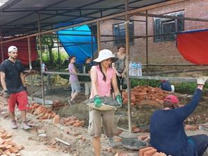 Un grupo de voluntarios poniendo ladrillos para construir una escuela en el Programa de Apoyo Humanitario en Nepal
