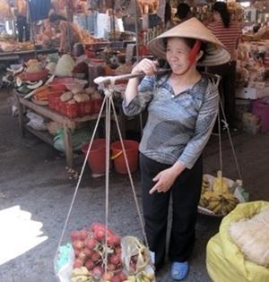 Una mujer vende frutas en un mercado local en Vietnam