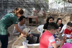 Una voluntaria de Projects Abroad ayuda un adolescente a acariciar a un perro en una sesión de terapia canina en Córdoba, Argentina