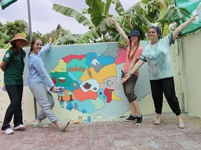 Un grupo de voluntarias muestran el resultado luego de pintar un mural para un centro de cuidado en el proyecto de Trabajo Social en Camboya