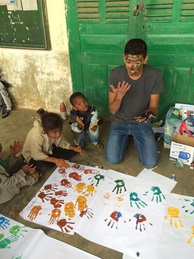 Niños locales y un voluntario pintando con los dedos en un centro para niños en el Madagascar