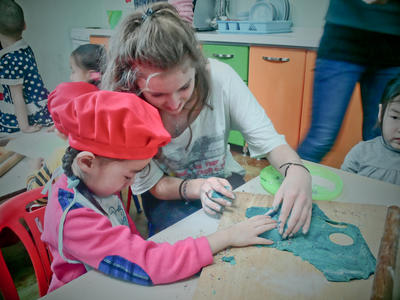 Voluntaria preparando galletas con niña en guardería en Mongolia