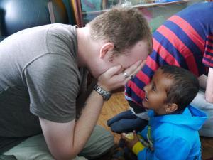 Un voluntario del proyecto de Trabajo Social juega con un niño pequeño en Nepal