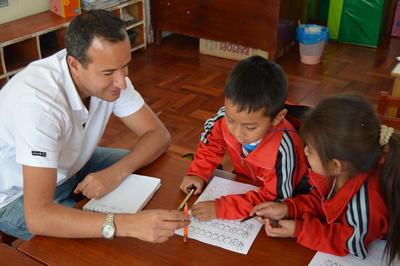 Voluntario ayuda a niños en proyecto de Trabajo Social en Perú