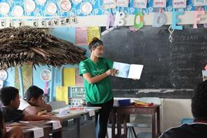 A Projects Abroad Samoa volunteers reads aloud to children at a Care placement.