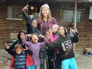 Voluntaria con unos niños durante el proyecto comunitario en Sudáfrica