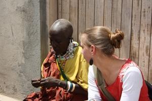 Voluntaria aprendiendo a hacer manualidades con local en Tanzania