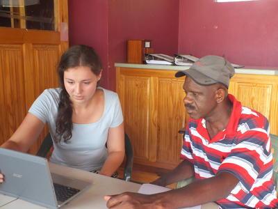 Voluntaria le muestra a local el programa de gestión de desastres