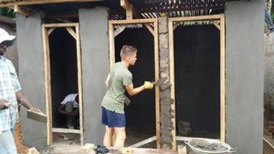 Voluntario joven ayudando en construcción de baños en Ghana