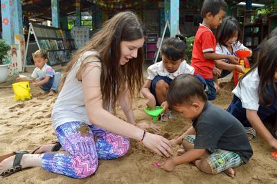 Joven voluntaria y niño jugando en un cajón de arena