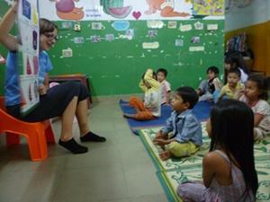 Un grupo de niños escucha atentamente a una voluntaria de Projects Abroad en Camboya