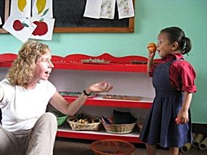 Una niña aprende mientras juega junto a una voluntaria en Nepal