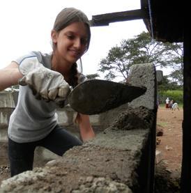 Voluntaria adolescente de Construcción colocando bloques en Tanzania
