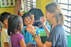 Voluntaria adolescente y niños haciendo manualidades en proyecto de Voluntariado Social en Filipinas