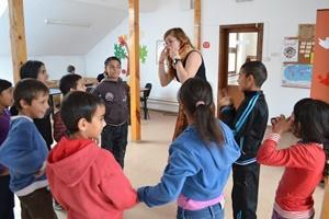 Voluntaria adolescente y niños durante juego educativo en Rumanía