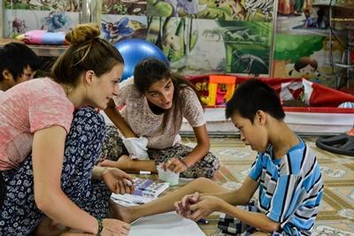 Voluntarias de Projects Abroad ayudan a un niño con necesidades especiales en una clase en Hanoi, Vietnam.