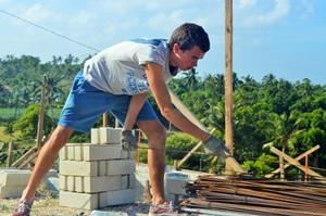 Un voluntario ayuda a construir una casa en Filipinas.