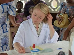 Voluntaria adolescente ayudando en el registro de dados en proyecto de Salud Pública y Francés en Togo