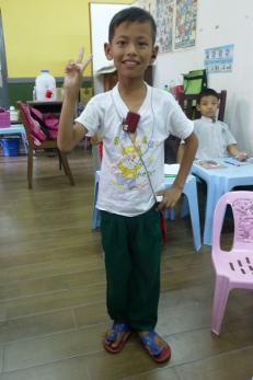Niño de una escuela local saludando en Myanmar, Asia.