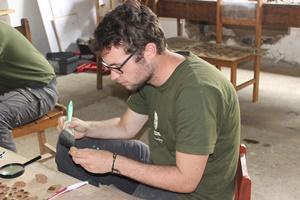 Un voluntario del proyecto de Arqueología para jóvenes entre 16-19 años trabajando con cerámicas.