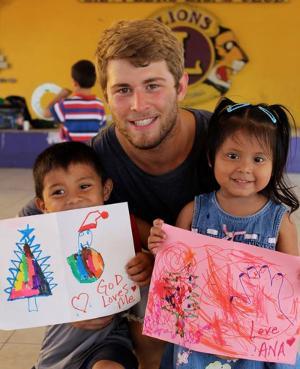 Un voluntario de Projects Abroad junto a niños locales y su trabajo de arte en Belice, Centro América.