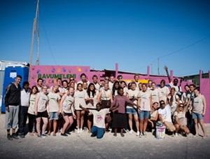 Voluntarios adolescentes junto a su proyecto completado de pintura en una escuela en el extranjero