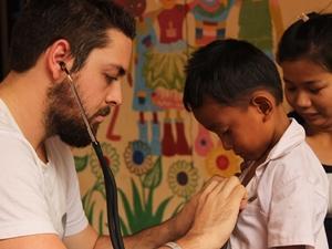 Voluntario de medicina de Projects Abroad trata a un niño como parte de un programa de asistencia médica en Nom Pen, Camboya