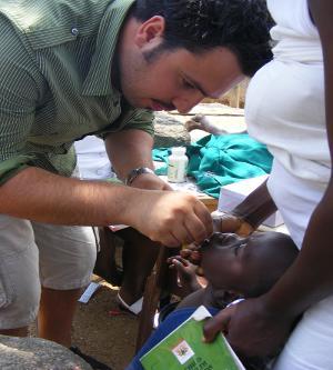 Voluntario realiza un chequeo dental a un niño en Ghana