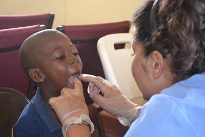 Una voluntaria de Projects Abroad en el proyecto de Odontología realiza evalúa a un niño en un programa de intervención comunitaria en Manchester, Jamaica.