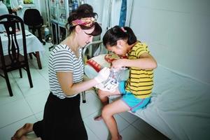 Una voluntaria ayudando a una niña en un programa de intervención comunitaria en Vietnam