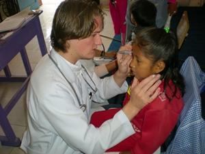 Un voluntario de medicina revisando a una chica en Bolivia, Sudamérica