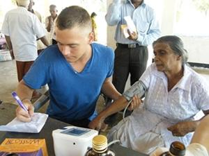 Interno de enfermería haciendo chequeo médico durante campaña de alcance médico en Sri Lanka