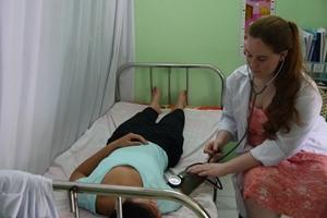 Una voluntaria del Proyecto de enfermería en Vietnam aprende cómo tomar signos vitales en un compañero interno.