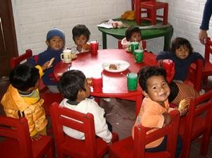 Niños comiendo alrededor de una mesa en Bolivia