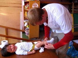 Voluntario de enfermería junto a un niño en Perú