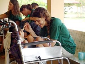 Una voluntaria alimenta a un niño discapacitado en el proyecto de Fisioterapia en Camboya