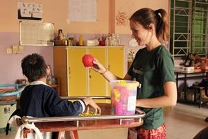 Una voluntaria del proyecto de Fisioterapia, realiza actividades con un niño en Camboya