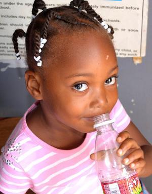 Niña bebiendo una botella de agua en el Proyecto de Medicina en Belice