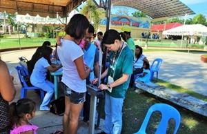Voluntaria pesando a su madre e hija como parte del proyecto de Salud Pública en Filipinas