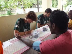 Una voluntaria de Projects Abroad mide la presión arterial de un hombre en Sri Lanka.