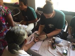 Una voluntaria comprueba los niveles de azúcar en la sangre de una mujer en Colombo, Sri Lanka