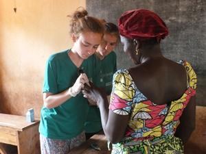 Dos voluntarios haciendo el test de diabetes durante una campaña médica en Togo