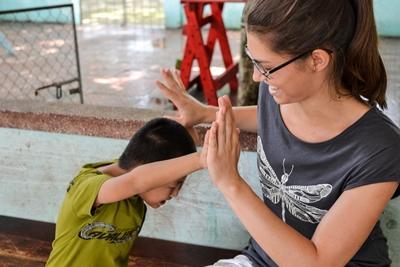 Voluntaria del proyecto de Logopedia de Projects Abroad trabaja jugando con un niños vitnamita en un centro de rehabilitación en Asia.