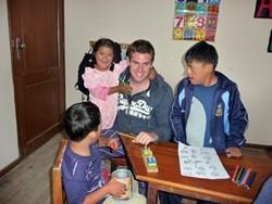 Profesor profesional voluntario con estudiantes en el proyecto de educación especial en Bolivia
