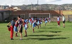 Alumnos de educación física calentando con un voluntario en Perú