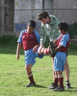 Profesor voluntario entrenando a estudiantes en una clase de educación física en Perú