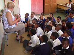 Voluntario enseña a niños pequeños en una escuela de Sudáfrica en el proyecto de enseñanza para profesionales
